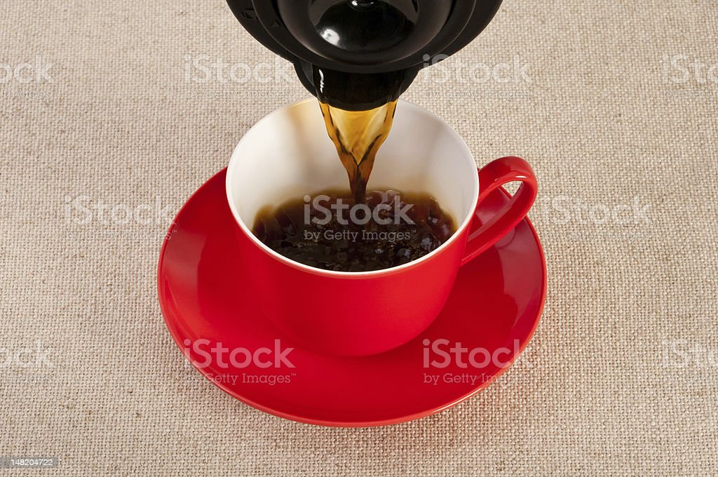 Hot coffee poured into a red cup royalty-free stock photo