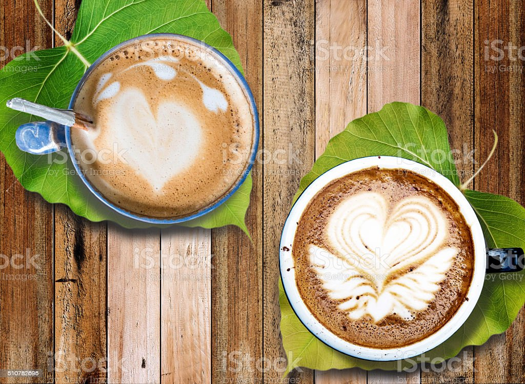Hot coffee with milk foam art with leaves under mugs stock photo