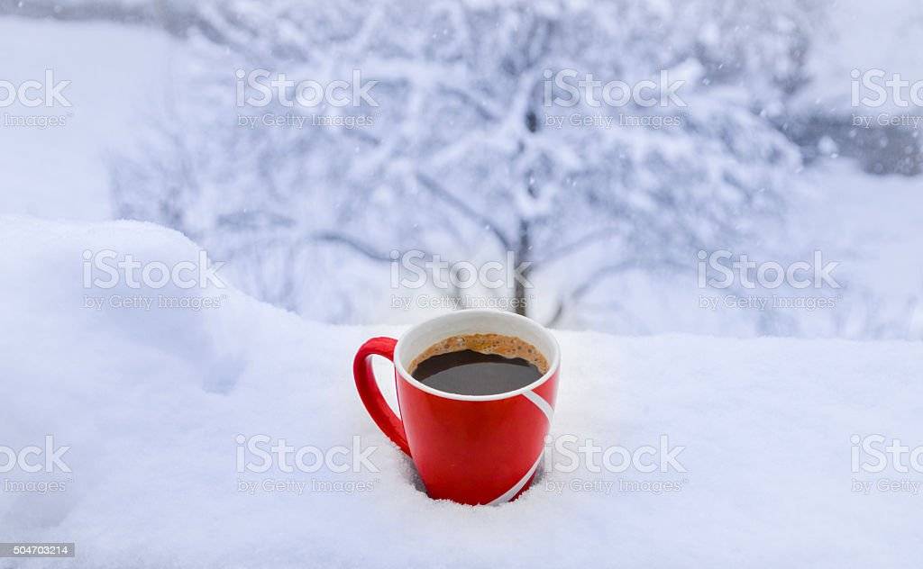 Hot cup of coffee on snow stock photo