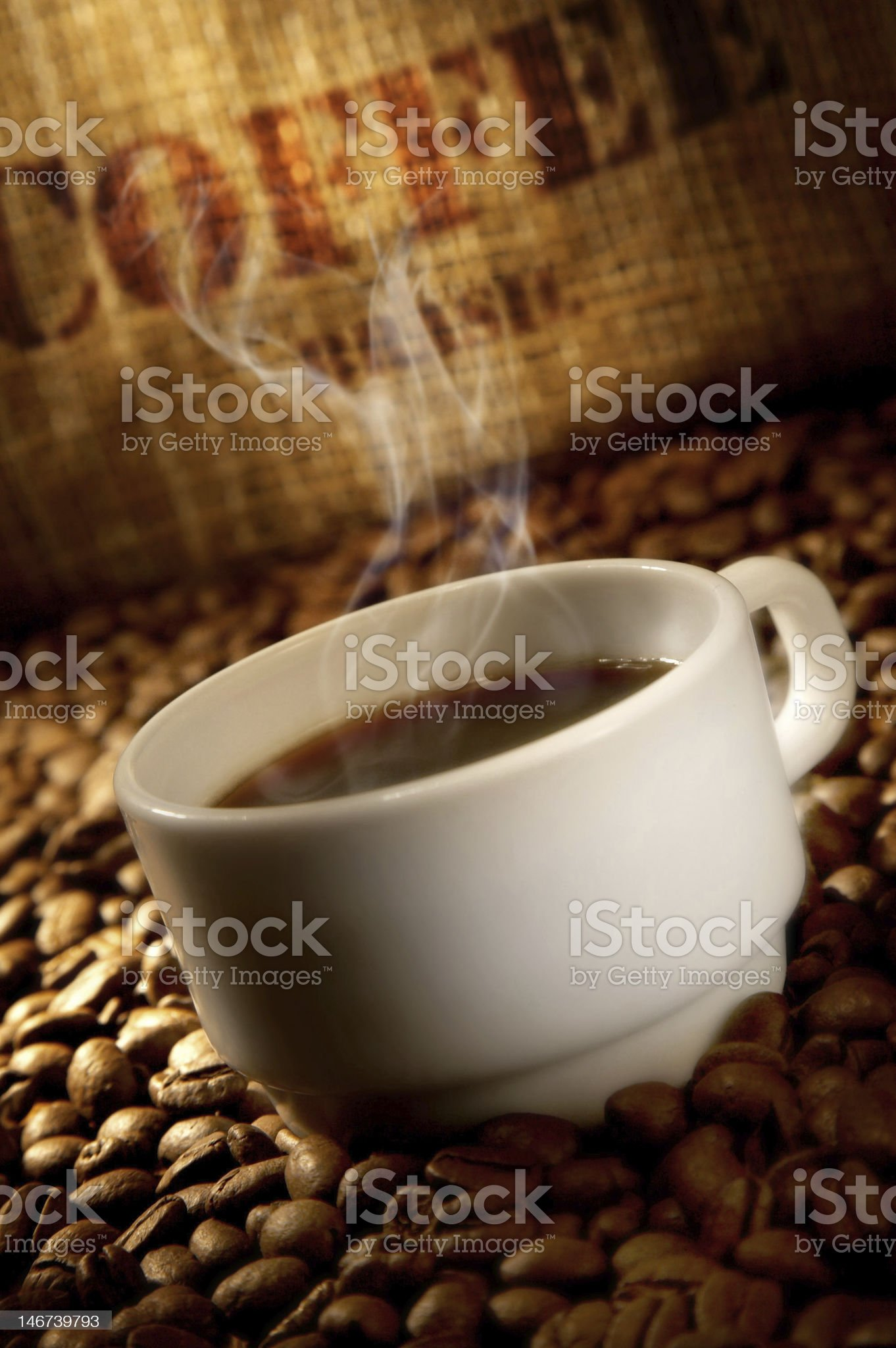 Hot cup of coffee standing in coffee beans royalty-free stock photo