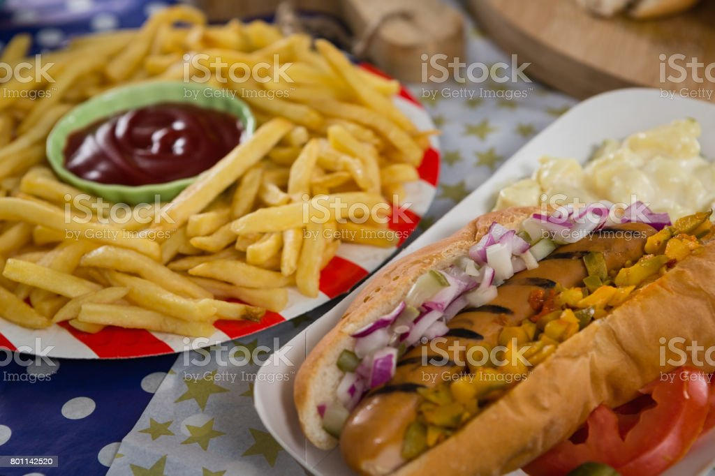 Hot dog and french fries on wooden table with 4th july theme stock photo