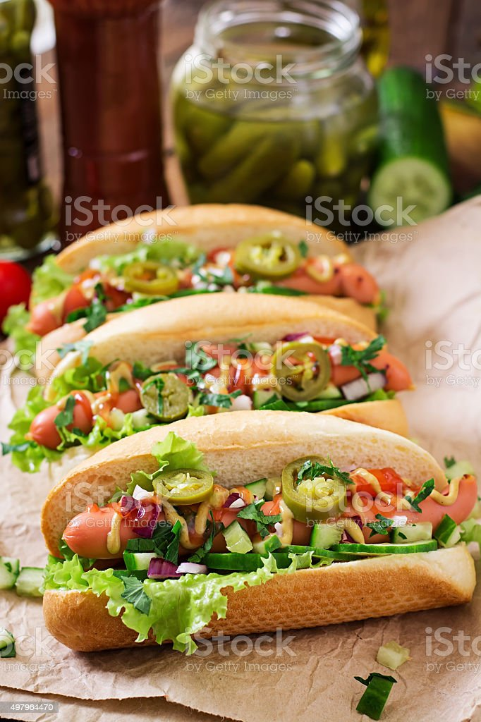 Hot dog with jalapeno peppers, tomato, cucumber and lettuce stock photo