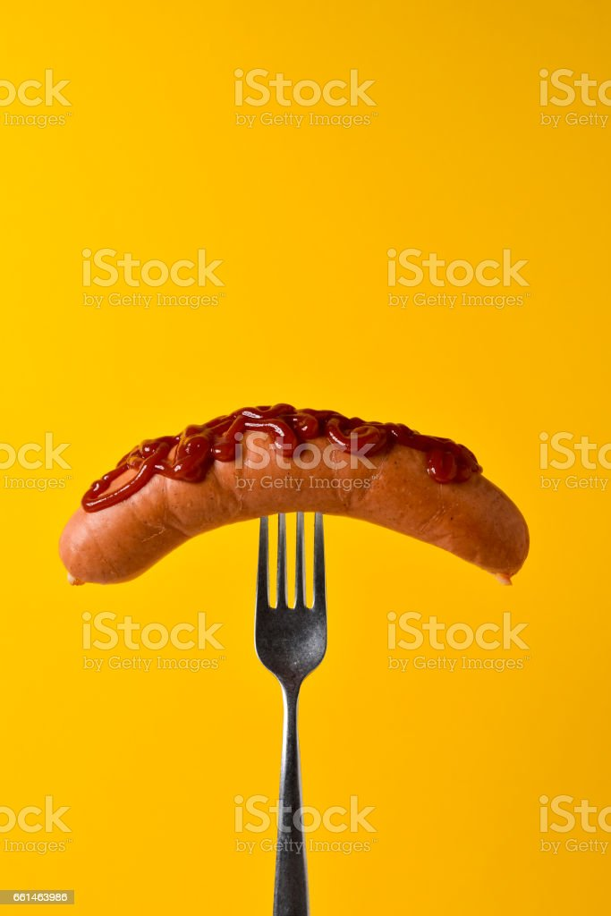hot dog with ketchup in a fork stock photo