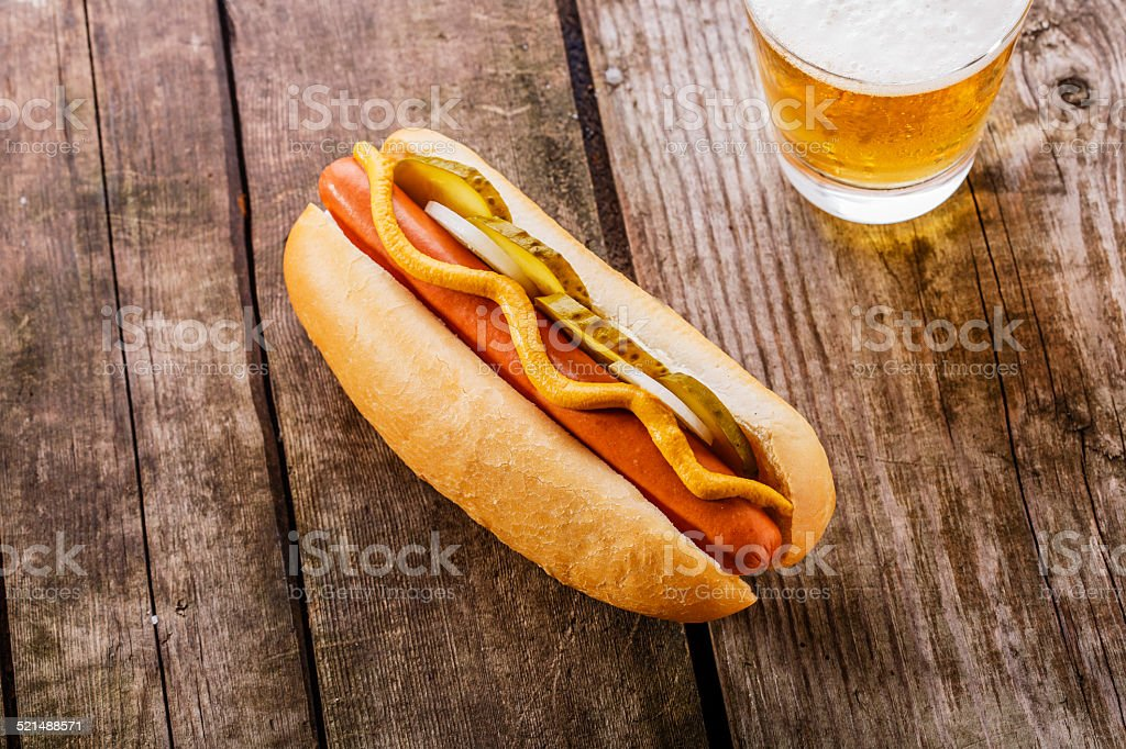 hot dog with mustard, pickles and onions stock photo
