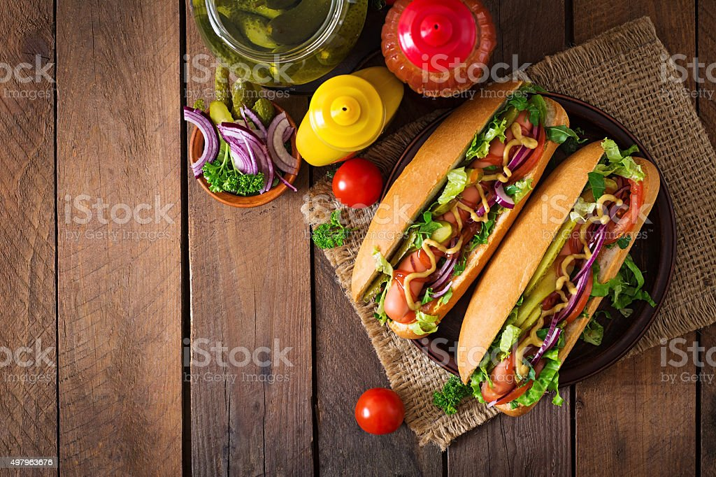 Hot dog with pickles, tomato and lettuce on wooden background stock photo