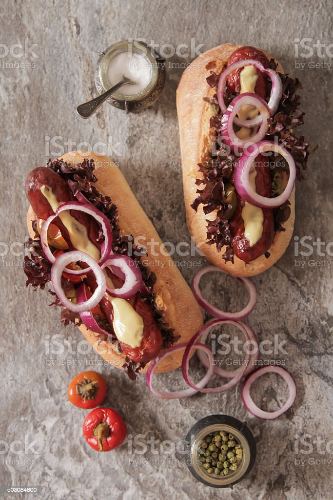 Hot dog with sausage and onions with salt red hot pepper stock photo