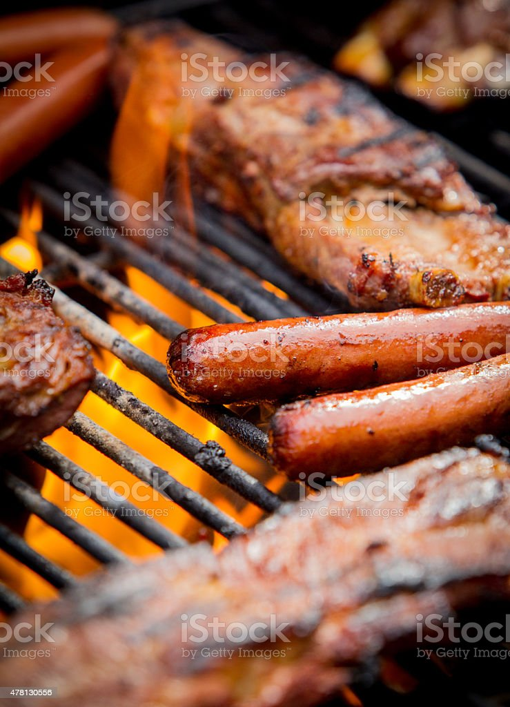 hot dogs and ribs on a grill stock photo