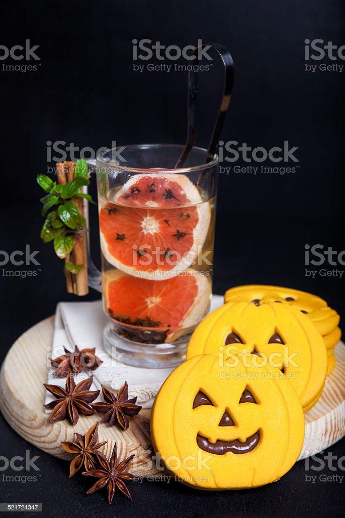 hot drink with red orange and halloween pumpkin cookies stock photo