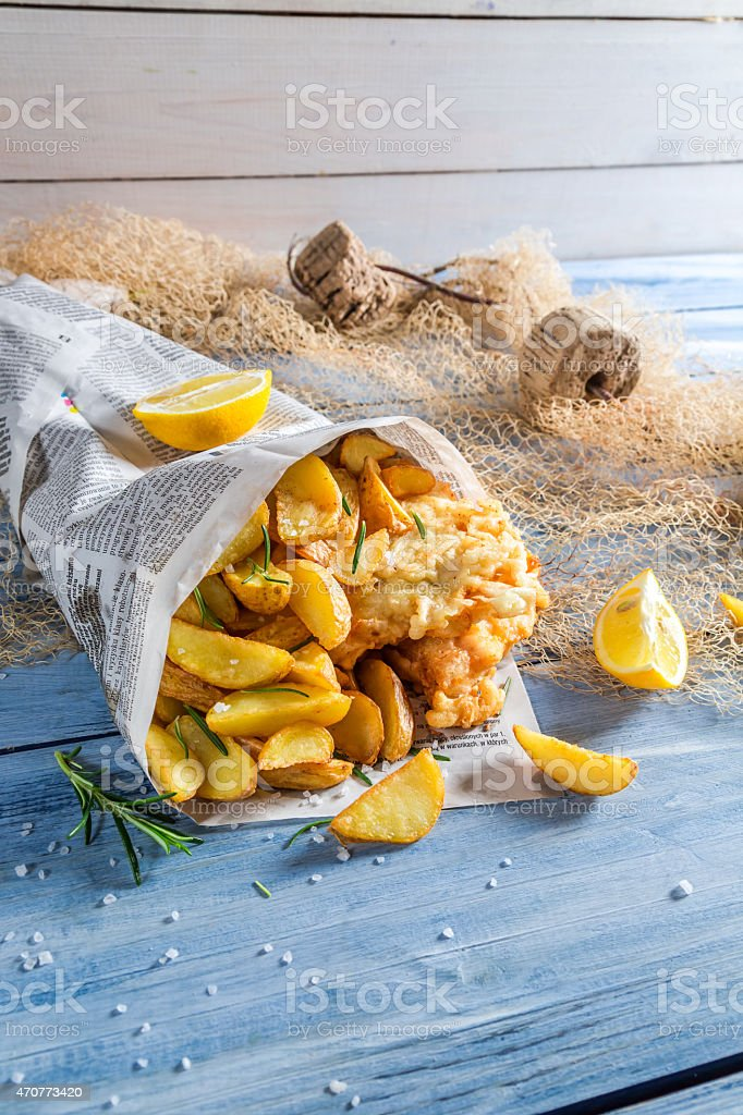 Hot fish cod with chips in newspaper with lemon stock photo