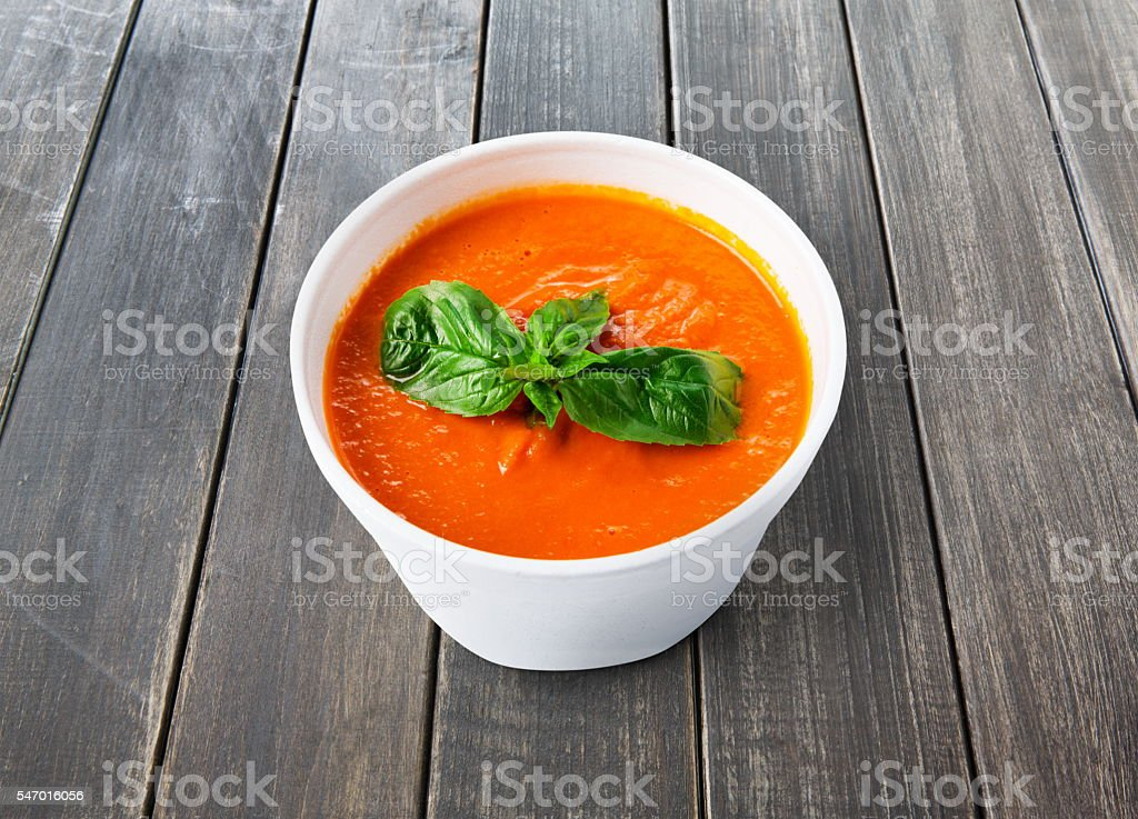Hot food delivery - tomato gazpacho soup at gray wood stock photo