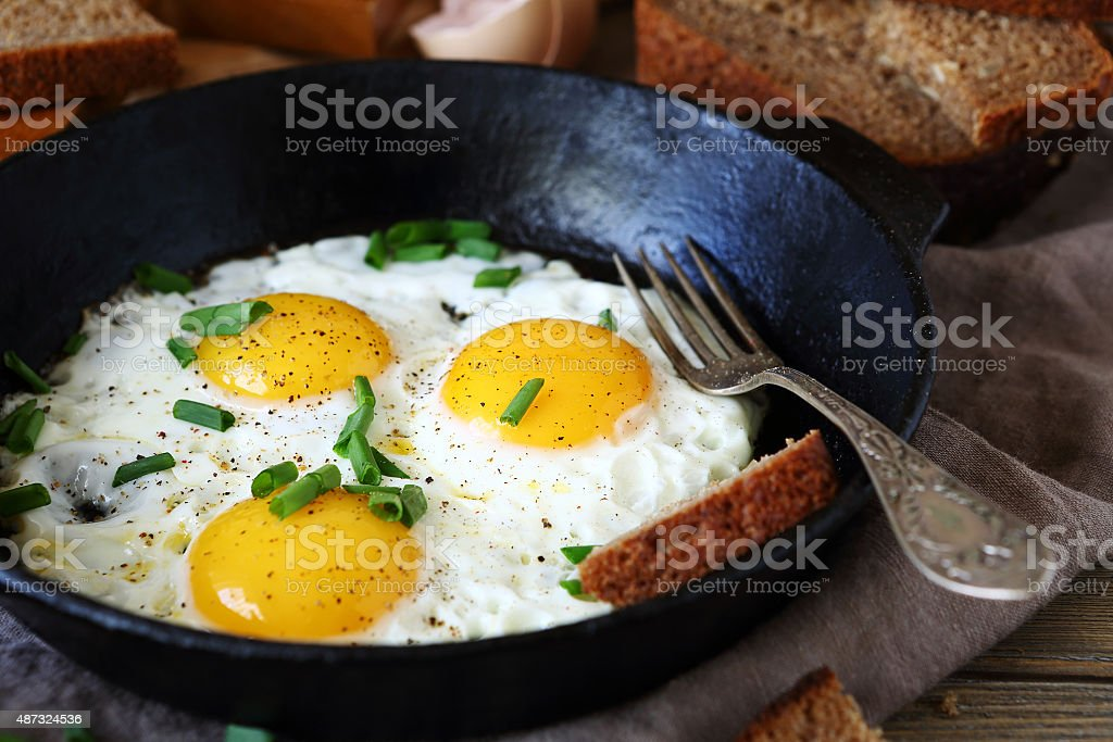 Hot fried eggs in a pan stock photo