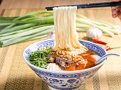 Hot instant noodles with cube beef and herbs on the