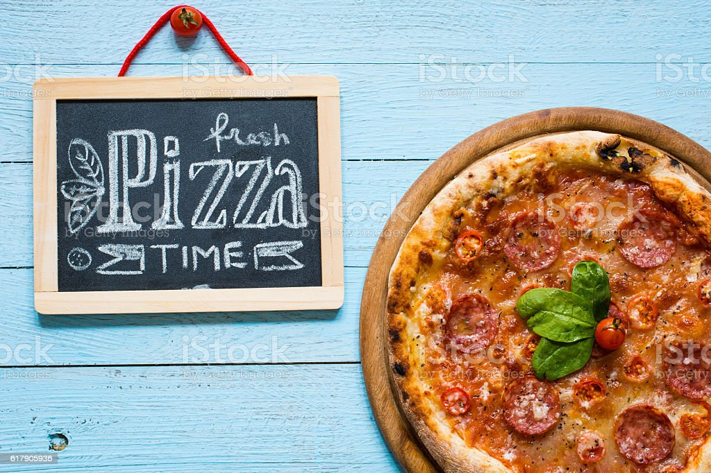 Hot Italian pizza on a rustic wooden table. stock photo