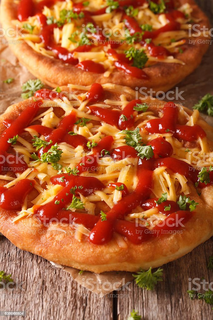Hot langos fried with cheese and ketchup macro. Vertical stock photo
