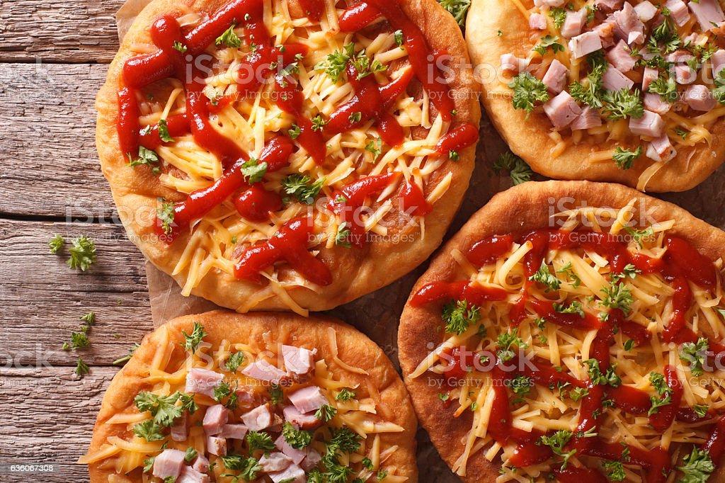 hot langos with cheese, ketchup and ham close-up. horizontal stock photo