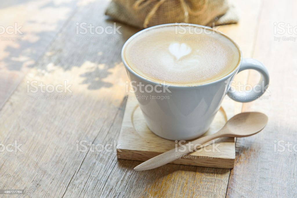 Hot latte coffee in glass  cup mug on wooden table stock photo