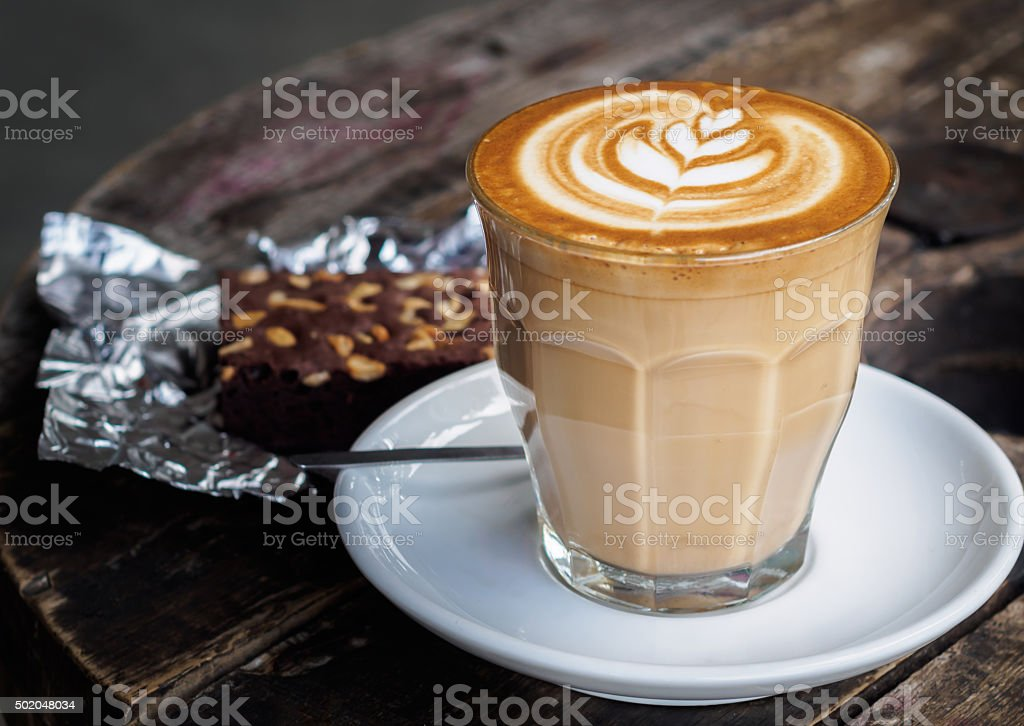 Hot latte coffee on old wooden table with brownie cake stock photo