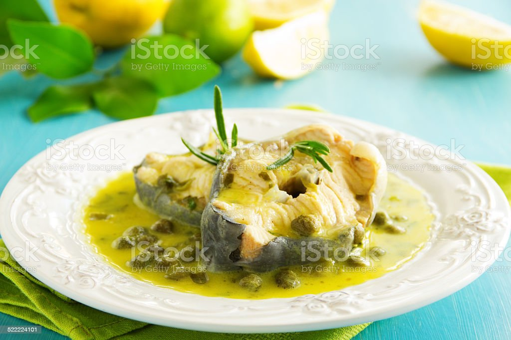 Hot lunch vapor sturgeon with lemon sauce and capers. stock photo