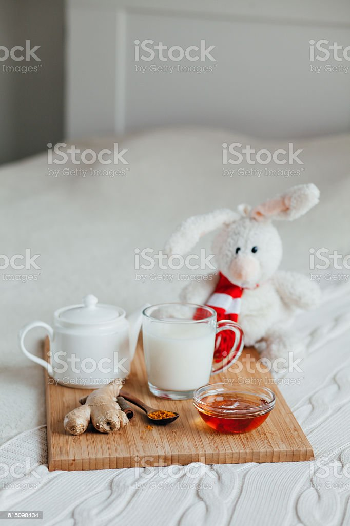 Hot milk in a glass cup and honey on  wooden stock photo
