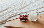 Hot milk in a glass cup and raspberry jam on