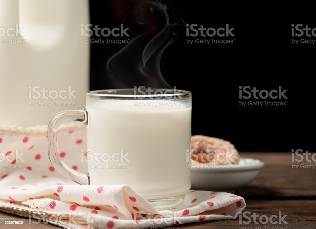 Hot milk in a glass with doughnut on wood stock photo