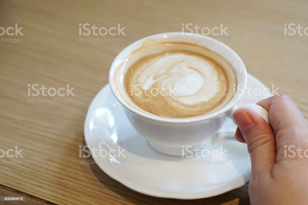 Hot Mocha - Closeup hand holding a cup of coffee with milk and latte art on wooden table. stock photo
