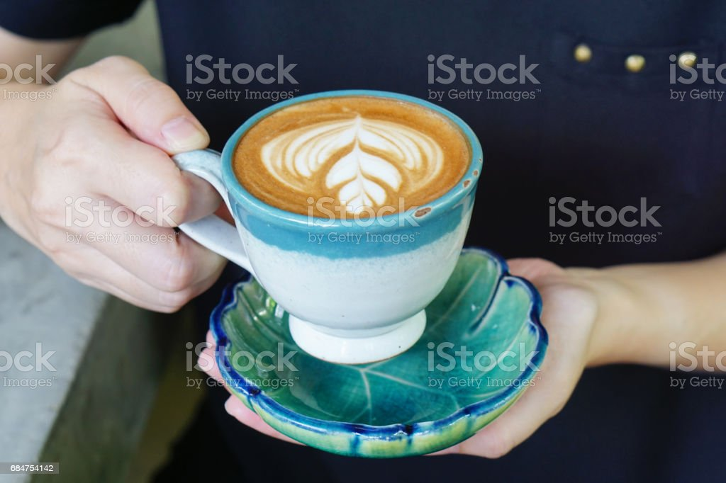 Hot Mocha - Woman holding a cup of coffee with beautiful latte art. stock photo