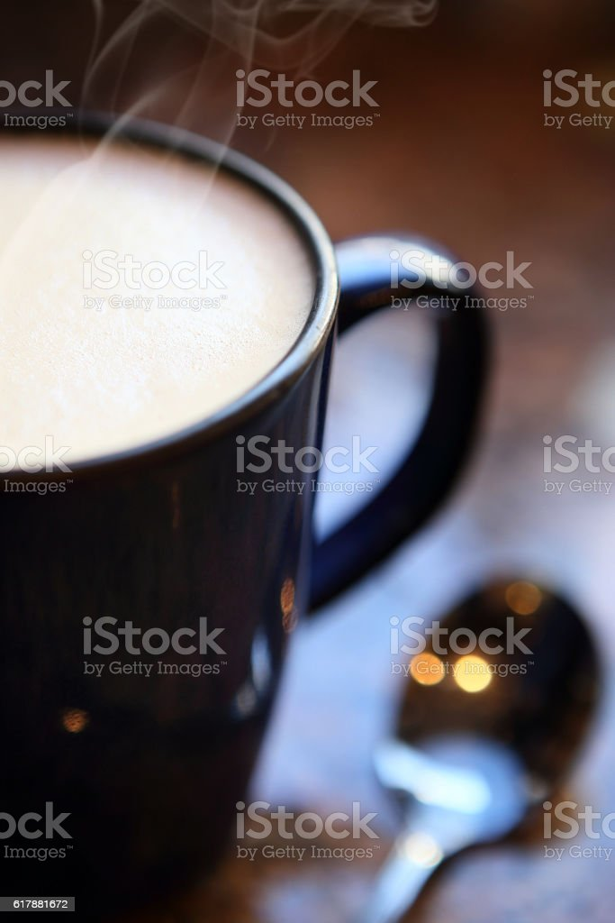 Hot mug of cappuccino with spoon, close up stock photo