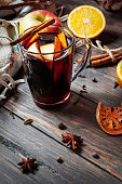 Hot mulled wine with spices, apple and orange on wood