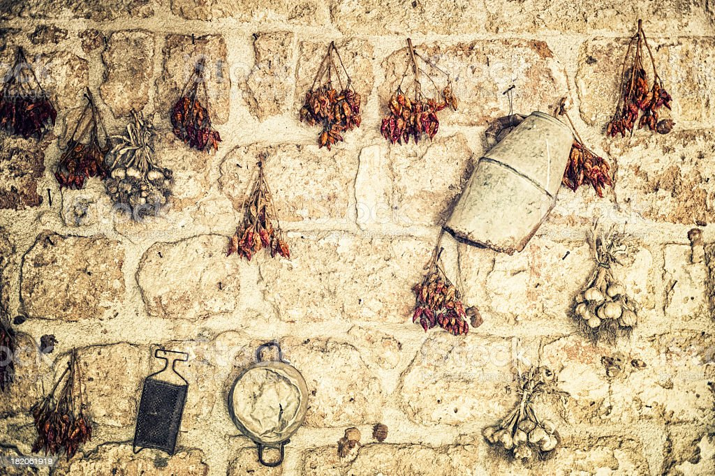 Hot peppers and garlic hanging on the wall, Italy royalty-free stock photo