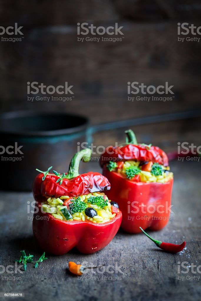 Hot peppers stuffed with rice and vegetables on dark background stock photo