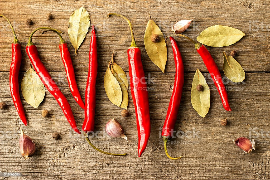 Hot peppers with spices on wooden table stock photo