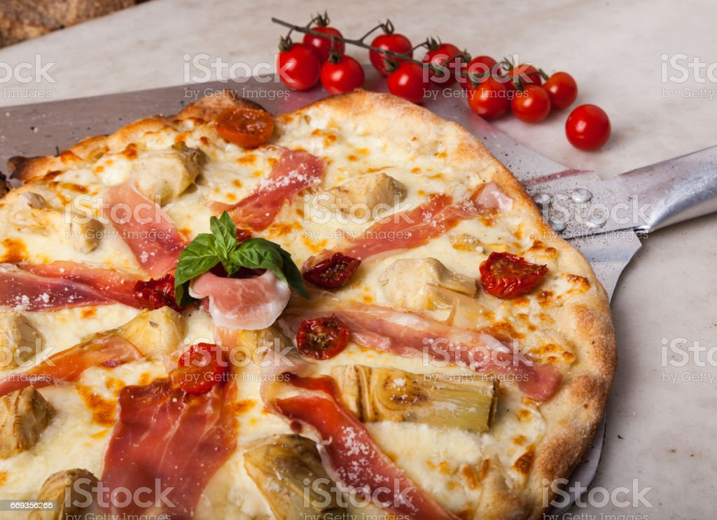 Hot pizza on a paddle, straight from the oven. stock photo