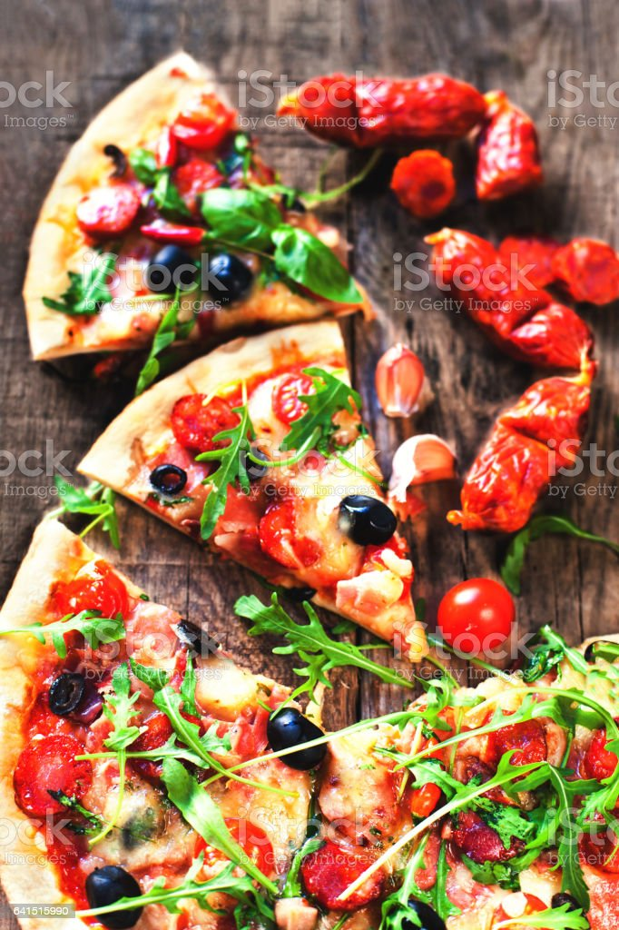 Hot pizza slice with Pepperoni, melting cheese on a rustic wooden table close up stock photo