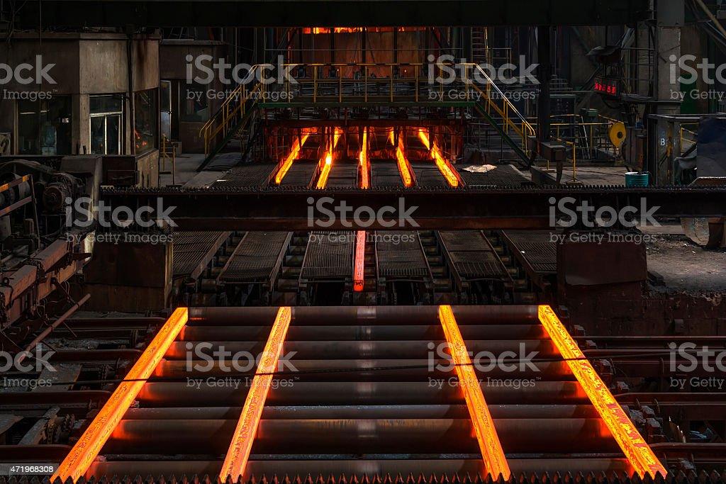 Hot steel on a conveyor belt inside of a factory stock photo