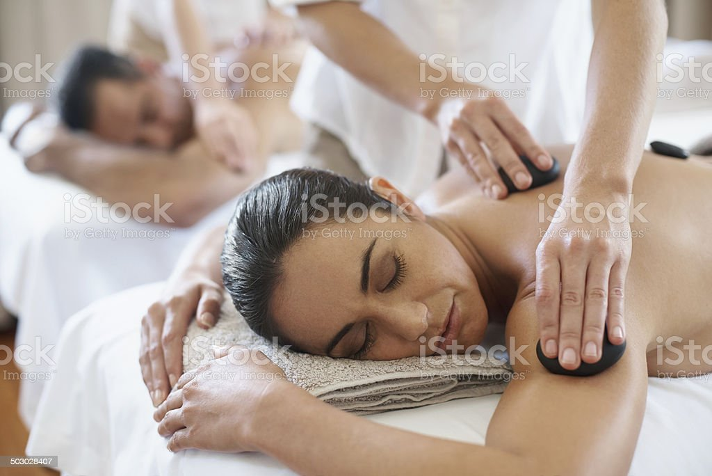 Hot stone therapy for deeper muscle relaxation stock photo