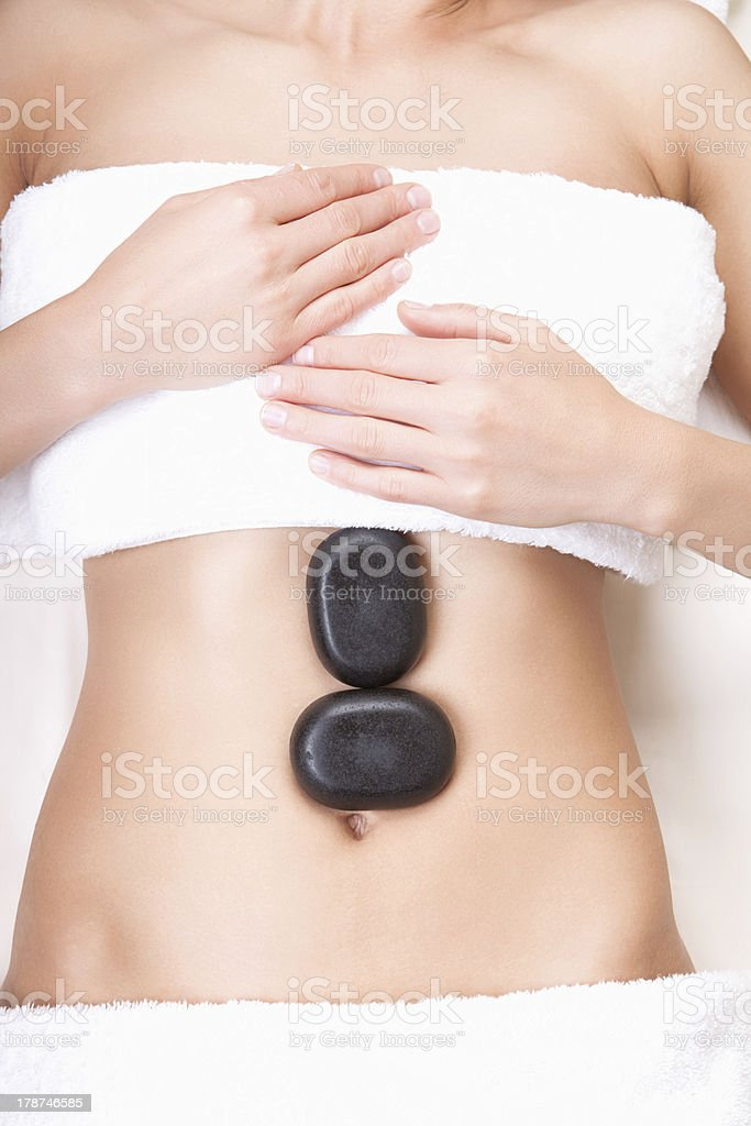 Hot stones on a woman's tummy royalty-free stock photo