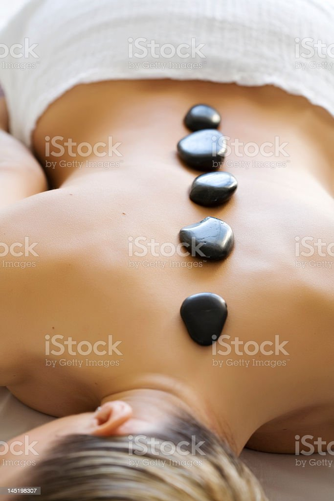 Hot stones therapy on a young lady's back stock photo