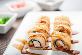 Hot sushi King maki with souce on a dish