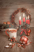Hot tea, Christmas cookies and candles on decorated table