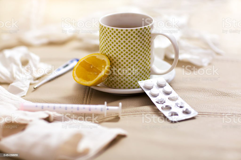 Hot tea for colds, pills  handkerchiefs and thermometer stock photo