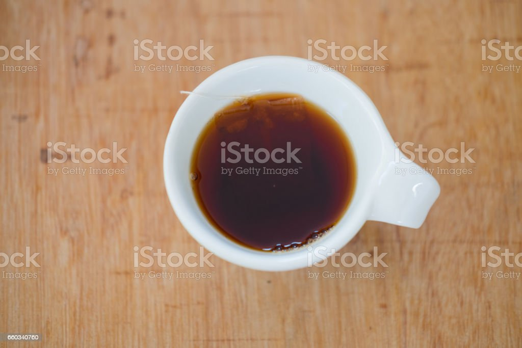 Hot tea in cup on wood table, top view stock photo