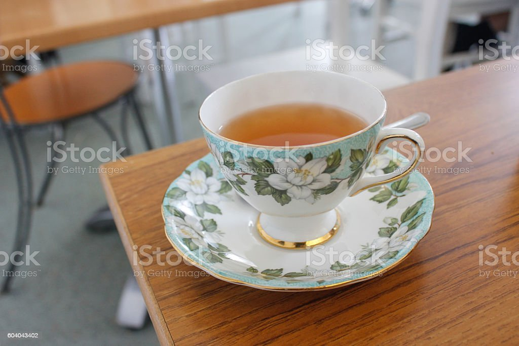 Hot tea in floral porcelain cup stock photo