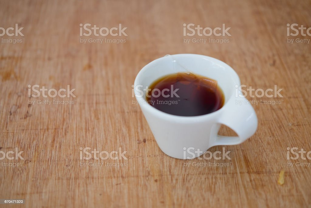 Hot tea in white ceramic cup on wood table stock photo