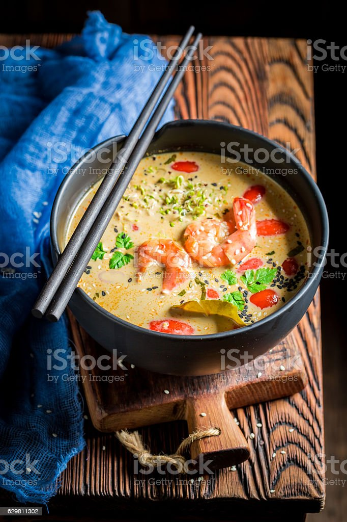 Hot Tom Yum soup in black bowl with chopsticks stock photo