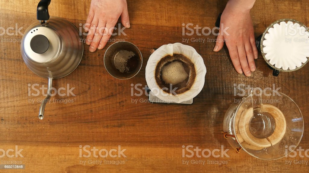 Hot water pouring trough coffee powder in the filter stock photo