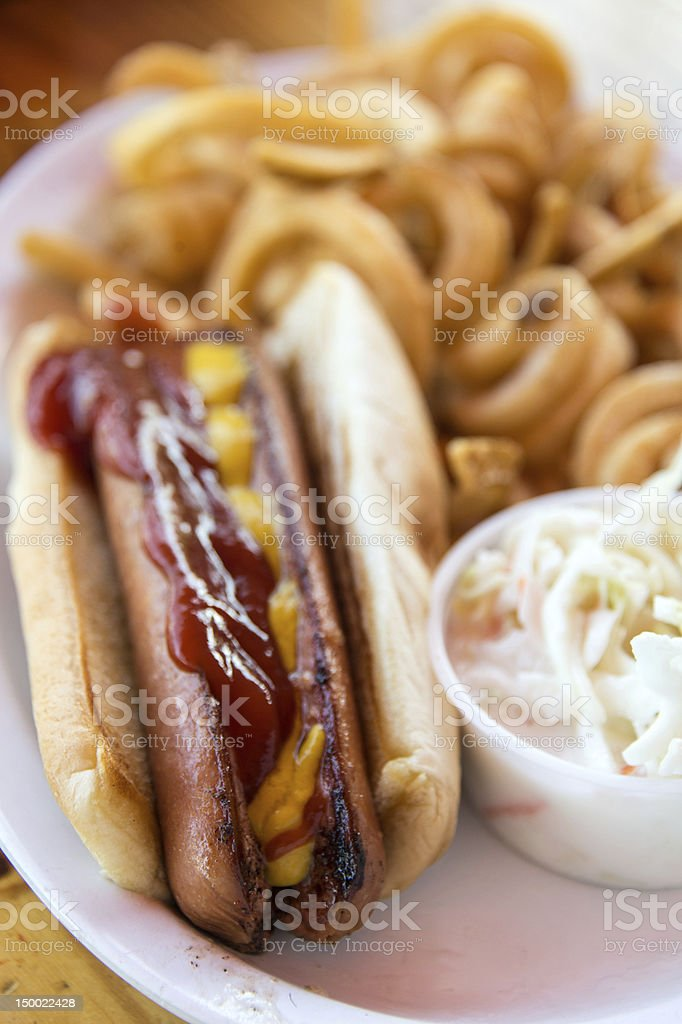 Hotdog served with curly fries and side order of coleslaw stock photo