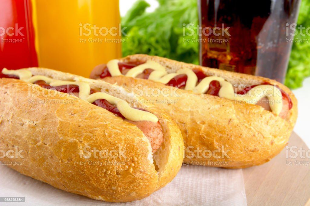 Hotdog with bottle of mustard,drink cola on wooden desk stock photo