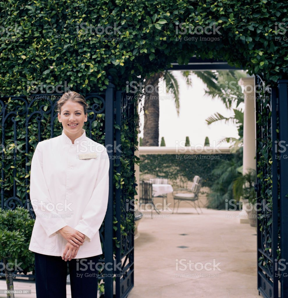 Hotel attendant standing by gate, portrait stock photo