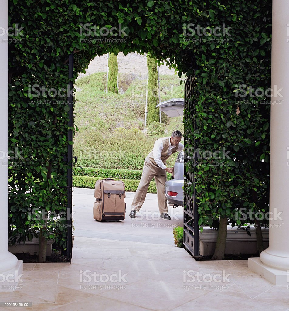 Hotel attendant unloading luggage from car stock photo
